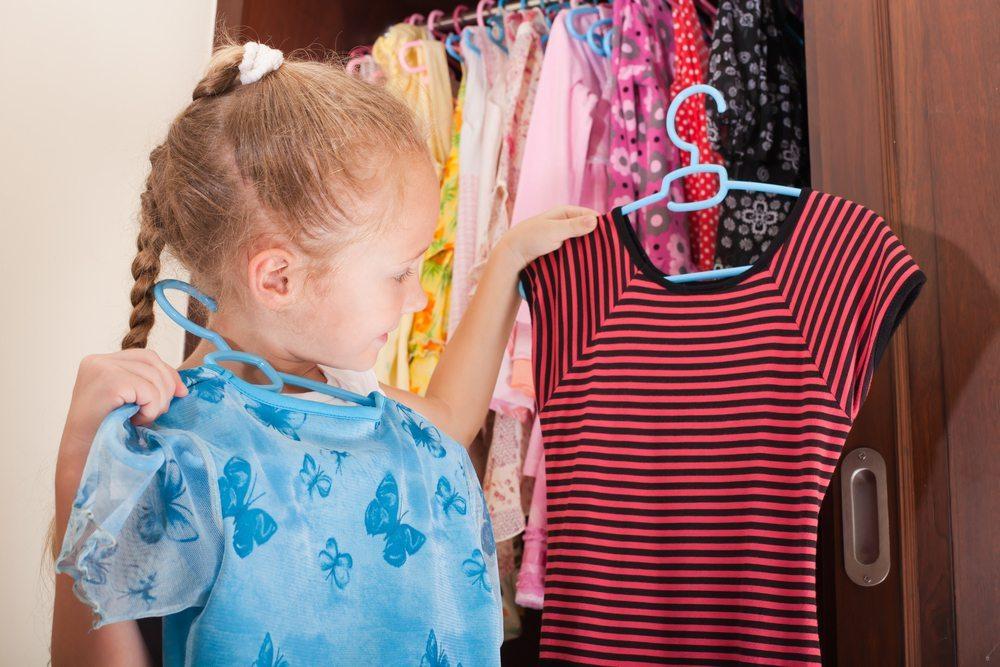 Damit der Nachwuchs sich morgens selbst ankleiden kann, gibt es spezielle Kindermöbel, deren Regalbretter und Kleiderstangen in der Höhe verstellbar sind. (Bild: altanaka / Shutterstock.com)