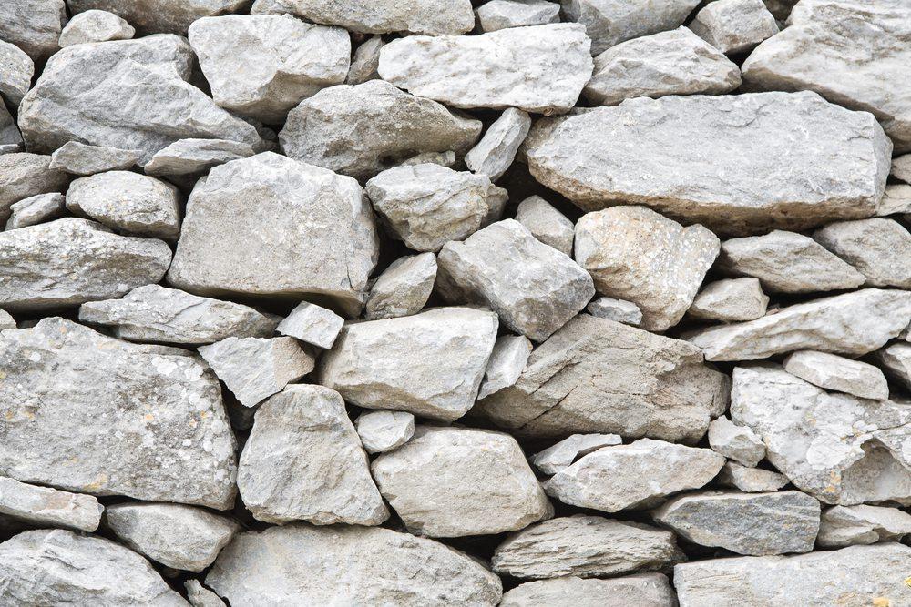 Eine Bruchsteinmauer kann als Trockenmauer an einer Böschung Blickfang in jedem naturnahen Garten sein. (Bild: Jeanette Dietl / Shutterstock.com)