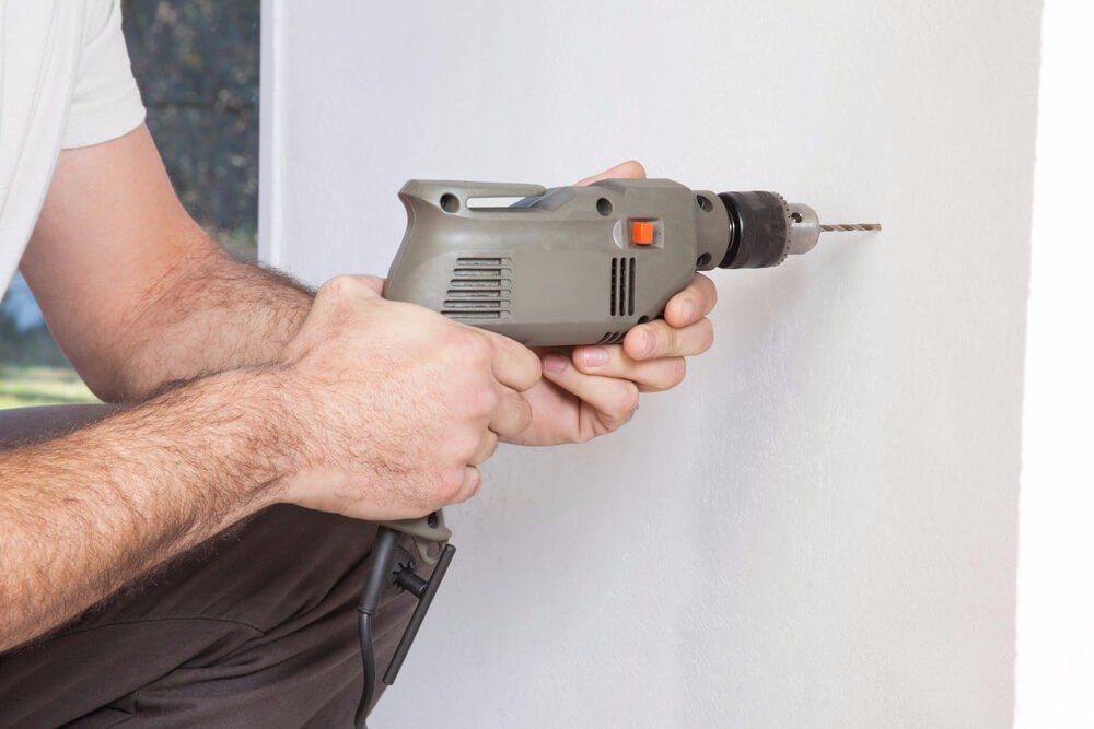 Um einen Dübel zu setzen, muss zunächst ein Loch in Wand oder Decke gebohrt werden. (Bild: © Tyler Olson - shutterstock.com)