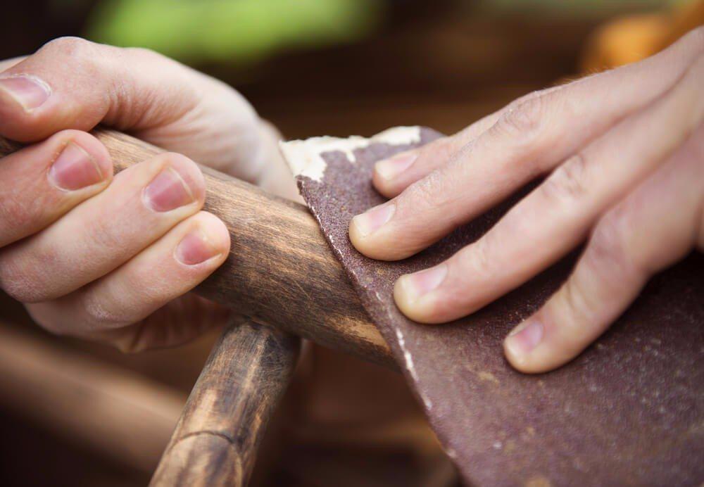 Das Abschleifen ist in der Regel die am besten geeignete Methode zur Lackentfernung auf alten Möbelstücken. (Bild: © Halfpoint - shutterstock.com)