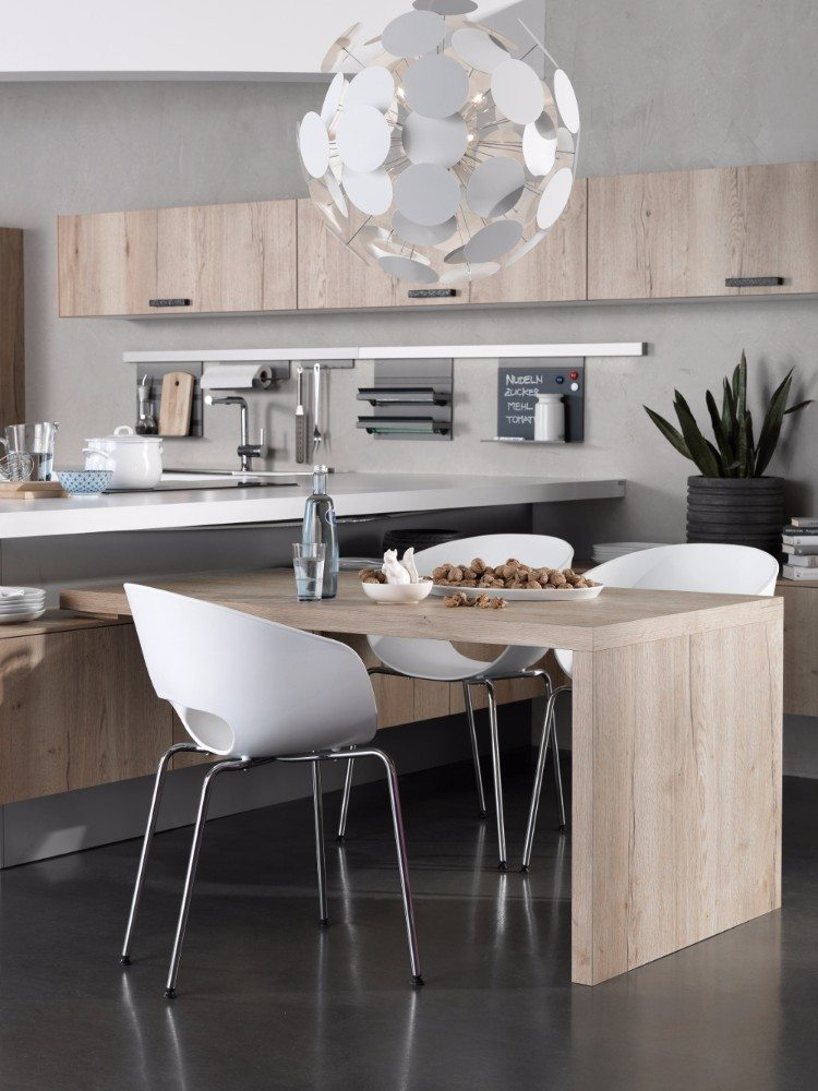 Einen formvollendeten optischen Abschluss der Koch-und Vorbereitungszone bildet diese gemütliche Essecke im rechten Winkel hierzu. Die Tischplatte liegt raffiniert auf den Unterschränken auf, was der gesamten Planung einen leicht schwebenden Charakter verleiht (rational, Modell lano).