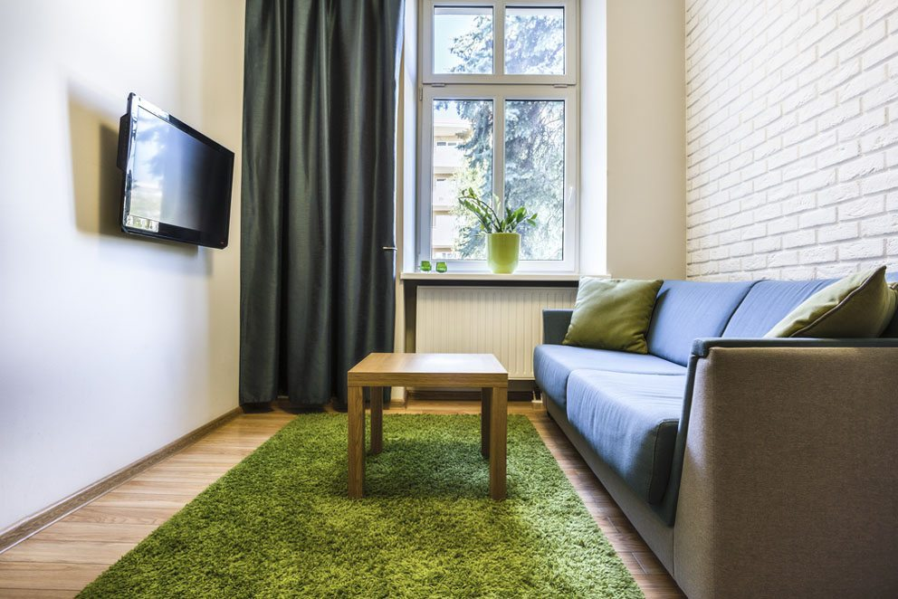 Bei den Vorhängen für eine junge Wohnung werden feste Stoffe bevorzugt, die das Schlafzimmer oder Appartement effektiv abdunkeln sollen. (Bild: Photographee.eu – Shutterstock.com)
