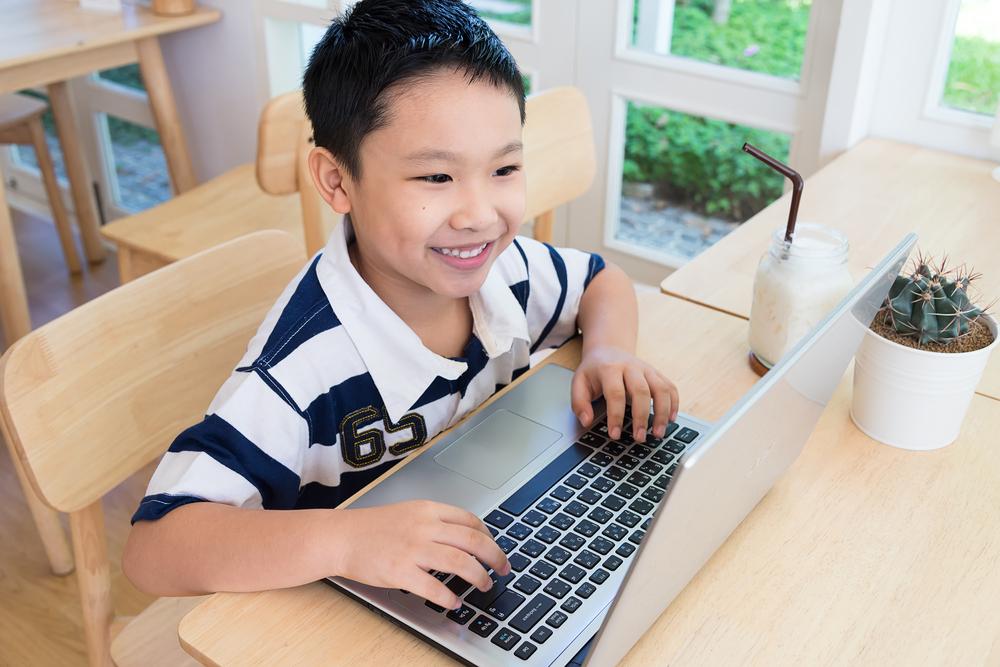 Kind sitzt vor dem Schreibtisch mit einem Laptop vor sich.