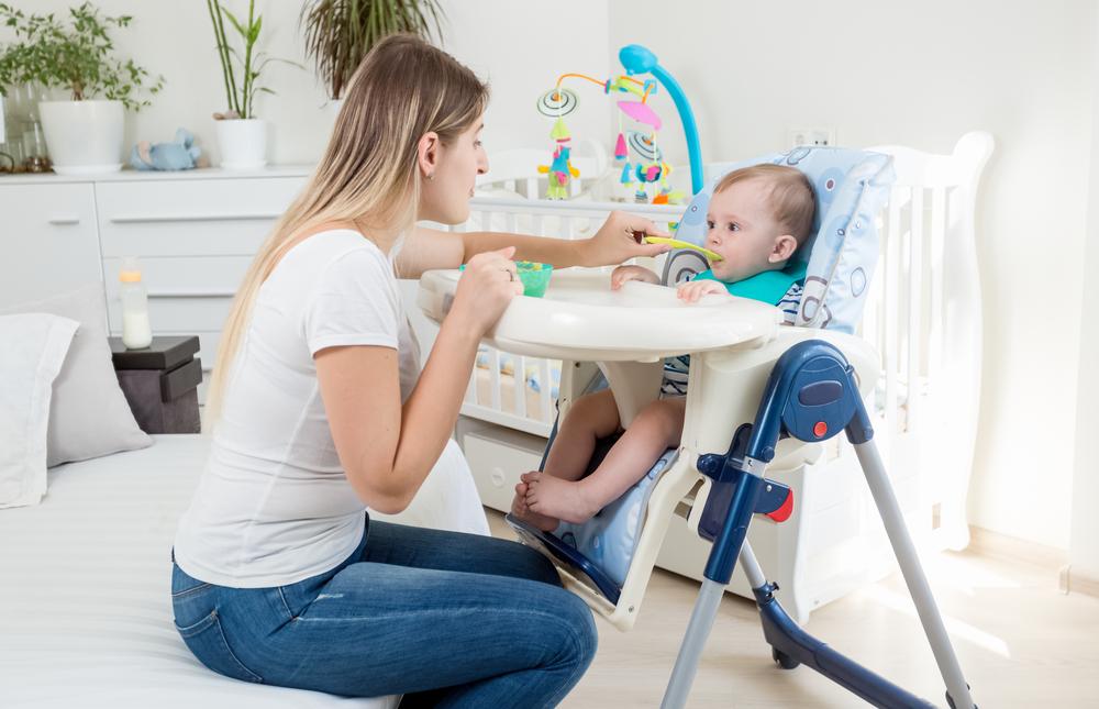 Schöne junge Mutter füttert ihren kleinen Jungen im Hochstuhl