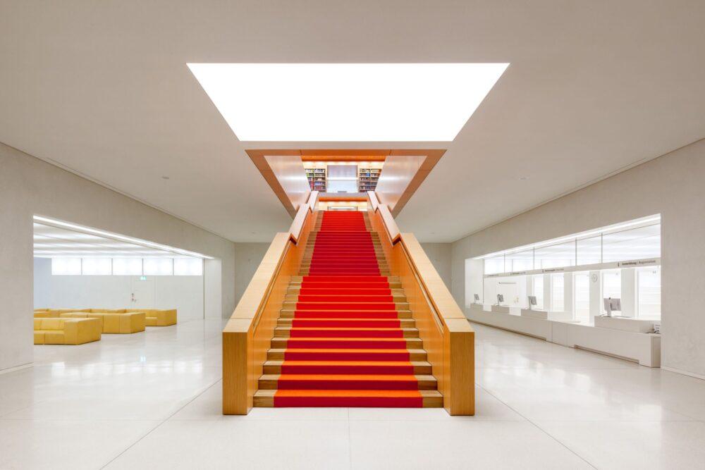 Die Haupttreppe der Bibliothek besticht durch den eleganten Kontrast von hellem Echtholzfurnier und orangener Wollfilzauflage.